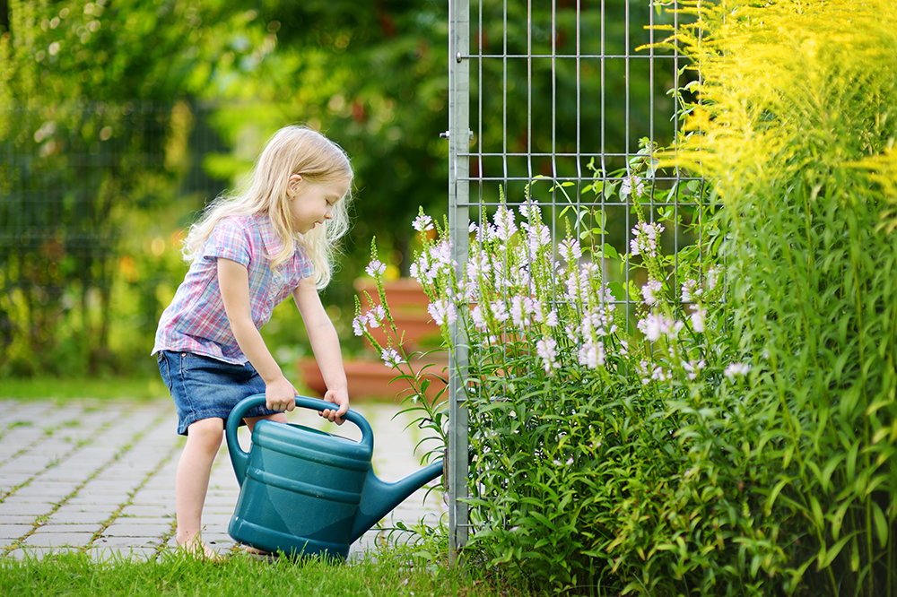 cute little girl watering flowers in the garden at a preschool & Daycare Childcare Center serving Thornton, CO