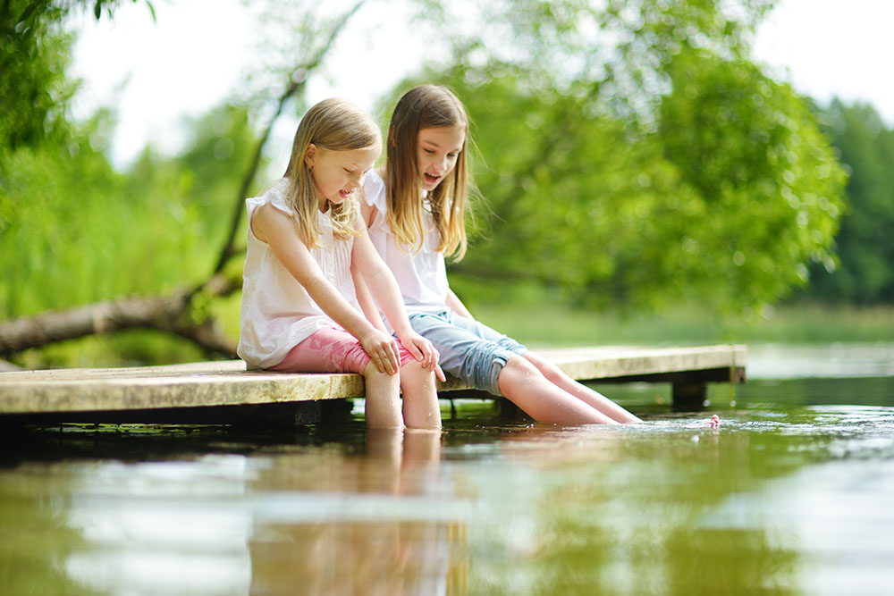 Two cute little girls sitting on a wooden platform by the river at a Preschool & Daycare Serving Thornton, CO San Antonio, TX