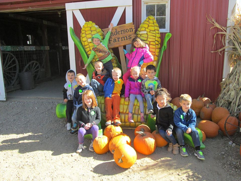 children sitting on pumpkins outside a farm at a Preschool & Daycare Serving Thornton, CO