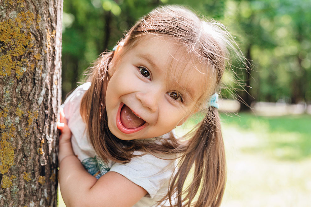 excited little girl laughing in park at a Preschool & Daycare Serving Thornton, CO
